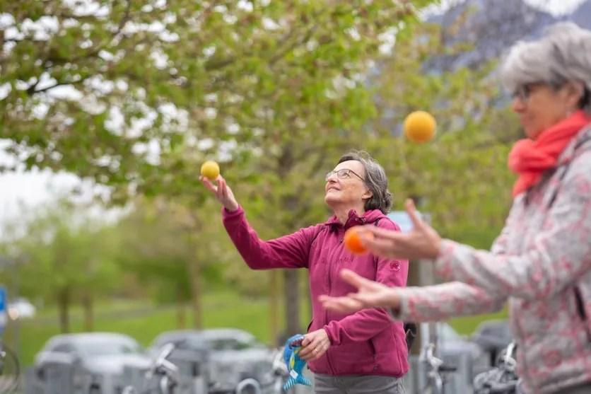 Koordinationstraining im Freien: Zwei ältere Frauen werfen bunte Bälle in die Luft.