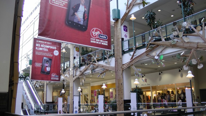 """Another generic photo of """"Fragile"""" by Roadsworth and Brian Armstrong at the Eaton Centre where I was unable to avoid the advertisement for Virgin mobile."""