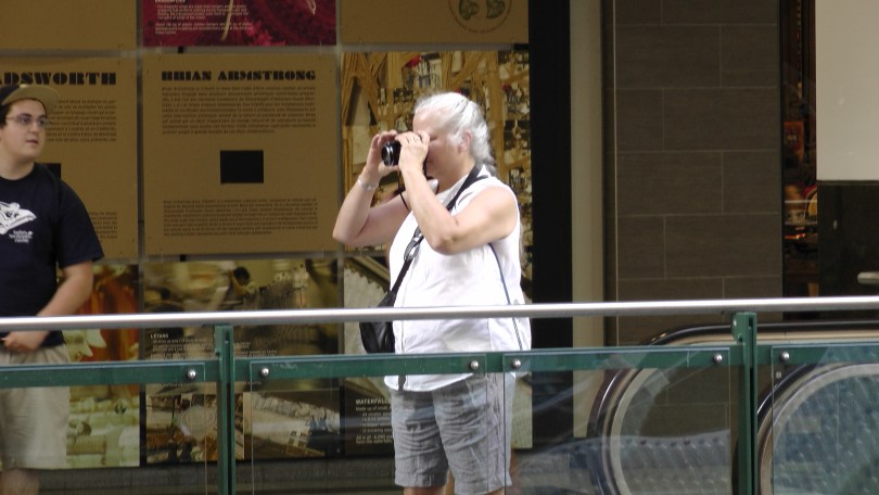 """Superfluous photo of an older woman taking a picture of """"Fragile"""" by Roadsworth and Brian Armstrong at the Eaton Centre."""