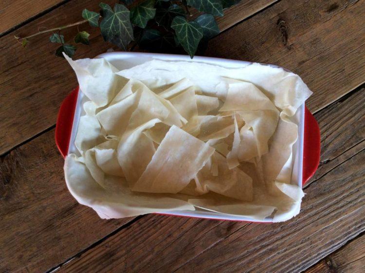 Викладаємо лист тіста та додаємо другий шар зі шматочків тіста