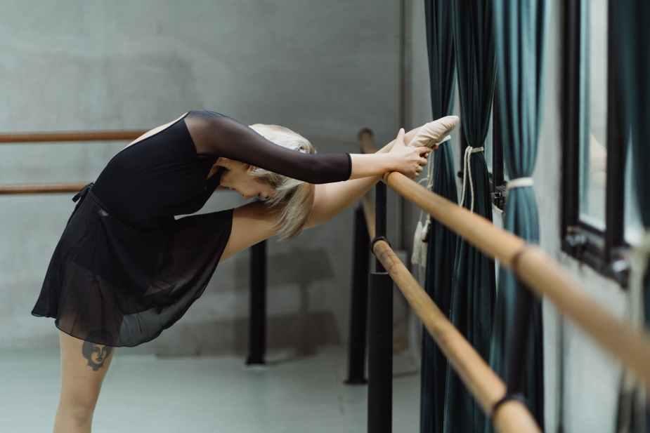 flexible young female dancer stretching legs near barre in studio