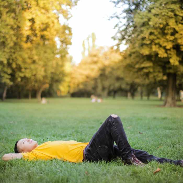 photo of man in yellow t shirt and black jeans lying down on green grass field with