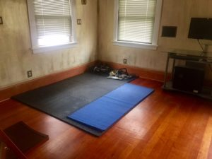"Photo of black mat on floor with weights nearby. Caption: ""Guest room turned into exercise space."""