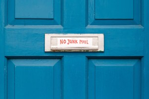Blue door with handwritten sign over mail slot: No Junk Mail