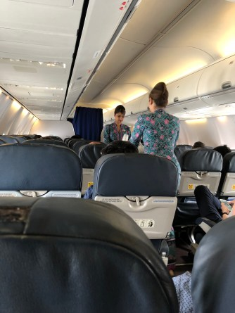 Flight attendants collecting trash from passengers prior to landing