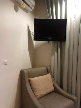 Arm chair and TV tucked in one corner of the bedroom