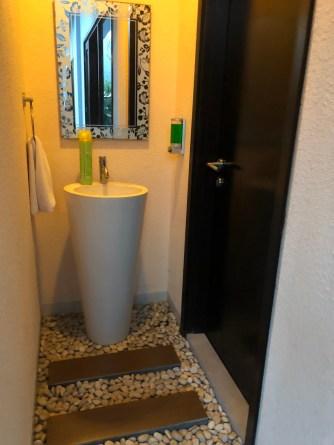 A small toilet next to the kitchen
