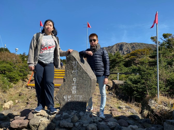 My friends with the tablet. The trek to the peak of Hallasan is behind this tablet