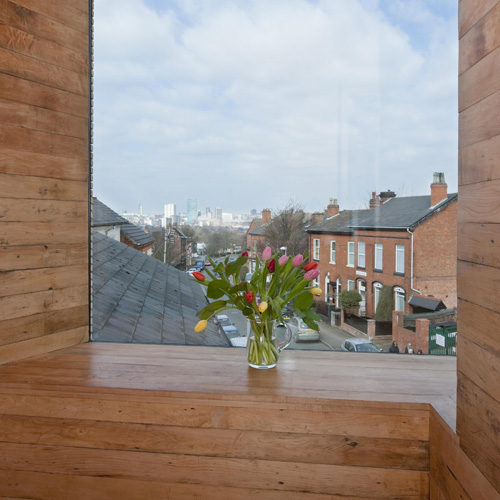 Tulips in a vase on the window sill of the alcove of the studio, zero carbon house, Birmingham with view of Tindal St