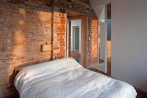 Bedroom in zero carbon house Birmingham with white duvet and sunlight on original bricks
