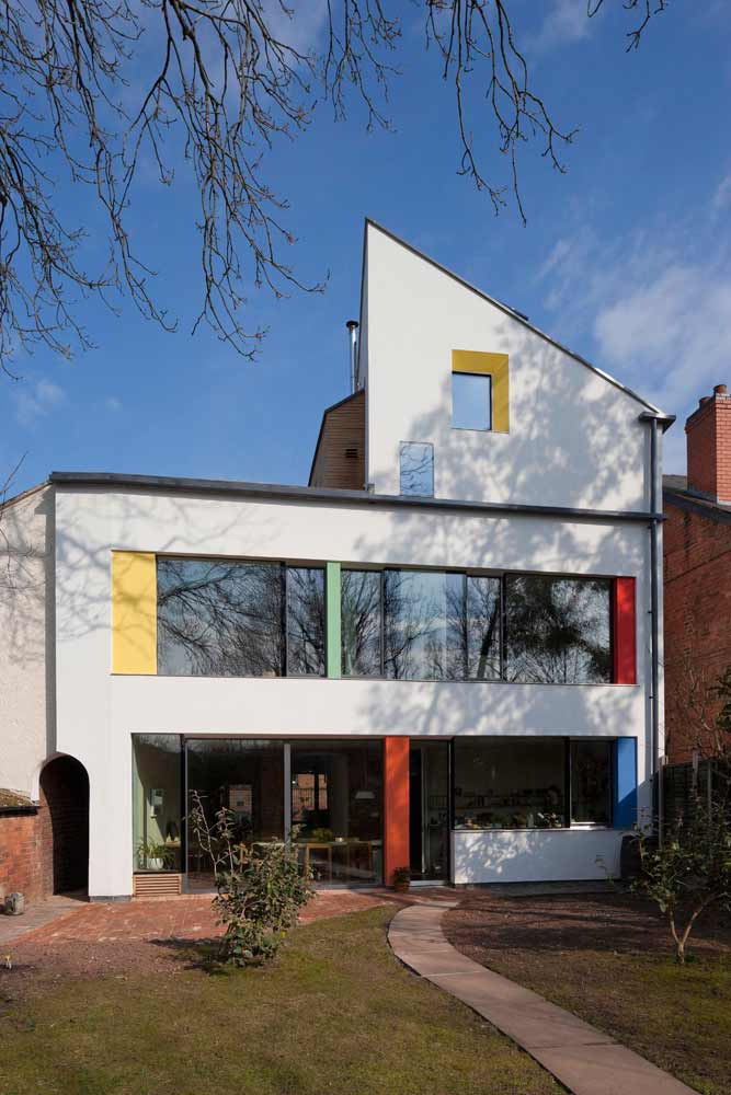 Back of the zero carbon house, Birmingham, as seen from the garden with red, yellow, blue and green splashes of colour on render