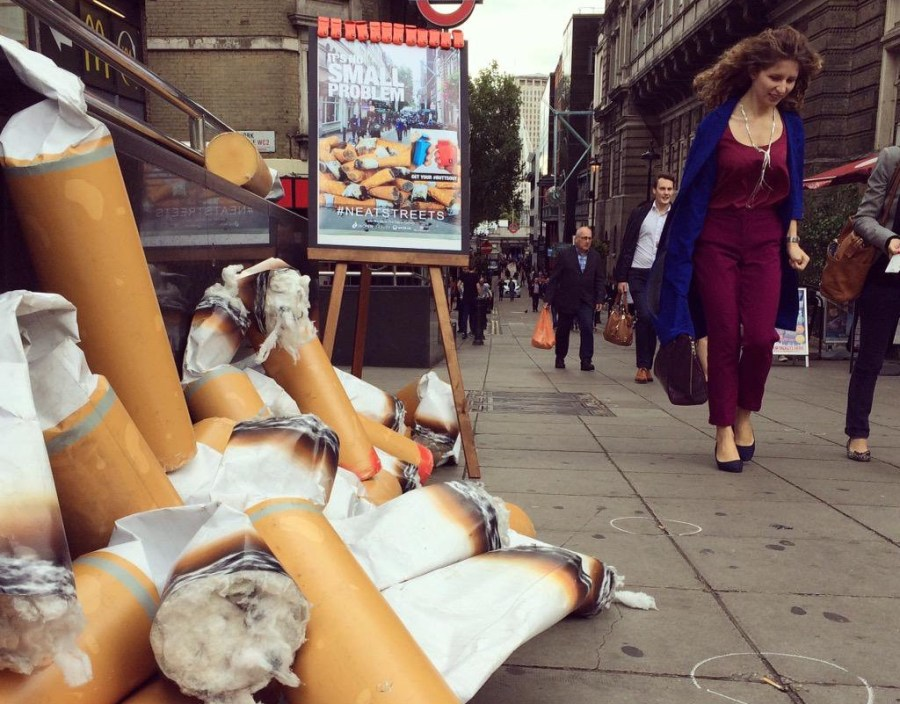 tas de mégot a taille humaine sur le trottoir avec des passants