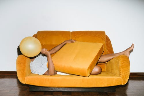 Person laying on sofa with a yellow balloon over his face