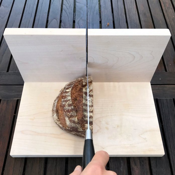 bread slicing guide with a loaf of sourdough bread