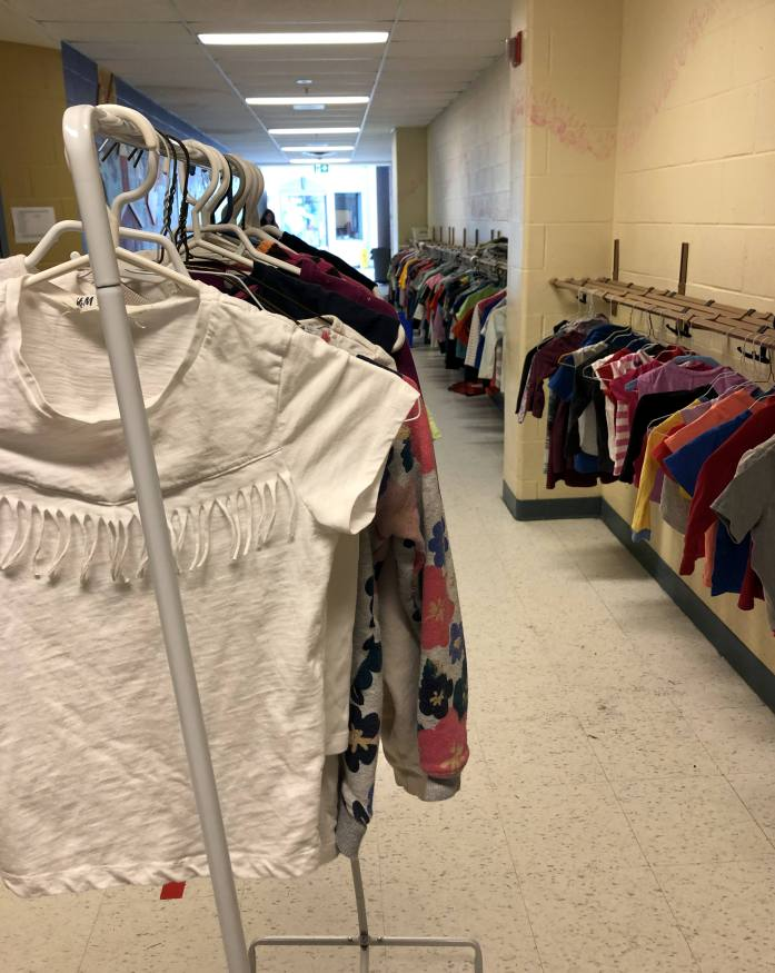 clothes hanging on racks in the hallway of a school for a secondhand clothing swap