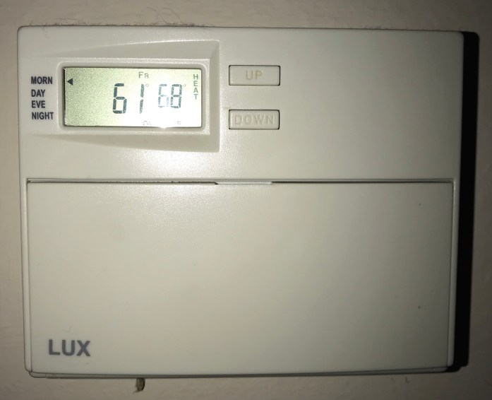a thermostat displays 61 degrees Fahrenheit indoors
