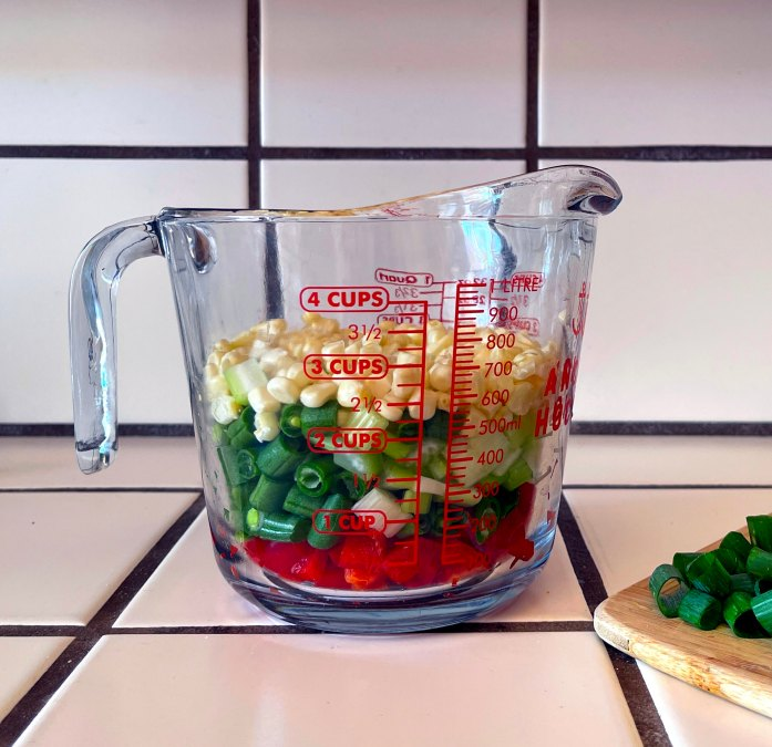 diced random vegetables in a measuring cup to make fried rice