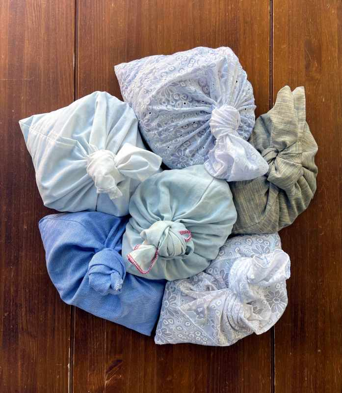 6 cloth produce bags sitting on a dark wooden table top. The bags are tied shut.