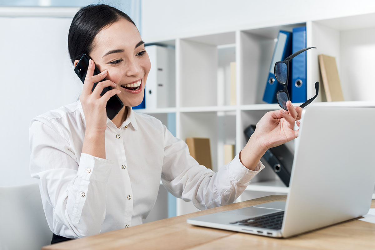 Image of customer service agent on the phone at her desk