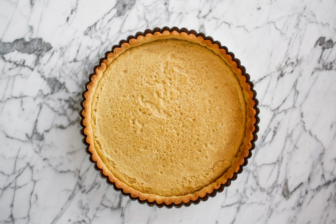 Tart pan lined with baked tart crust set on top of a marble surface.