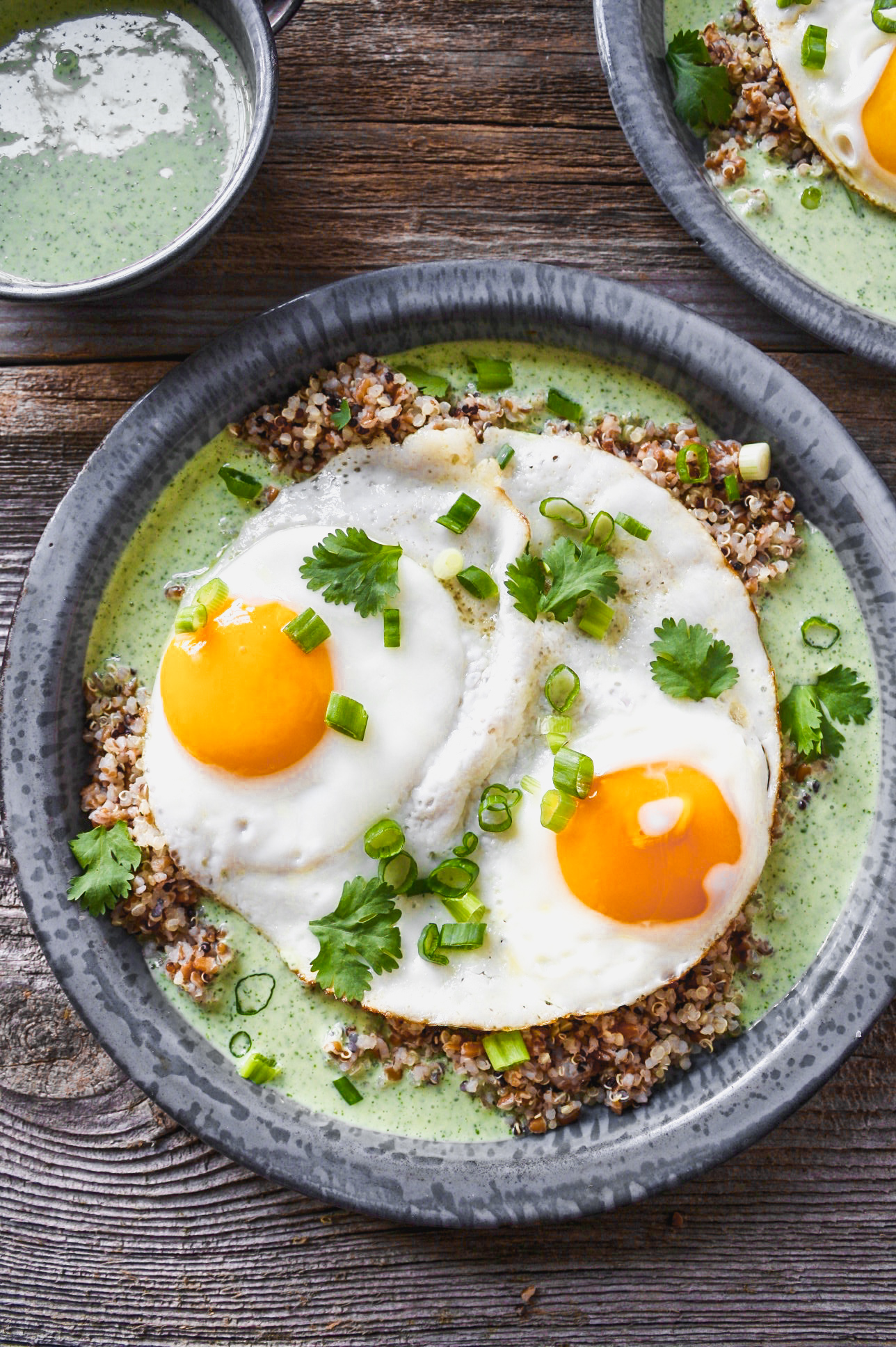 A gray metal plate with green sauce, grains, and sunny side up eggs, set on top of worn wood slabs.