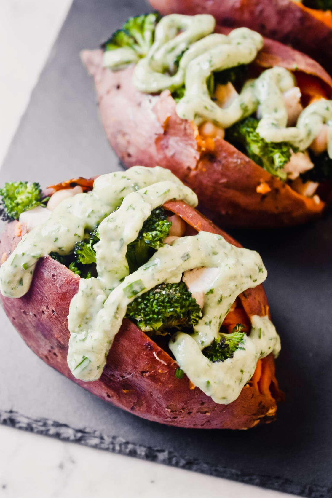 photograph of stuffed sweet potatoes drizzled with a green goddess dressing