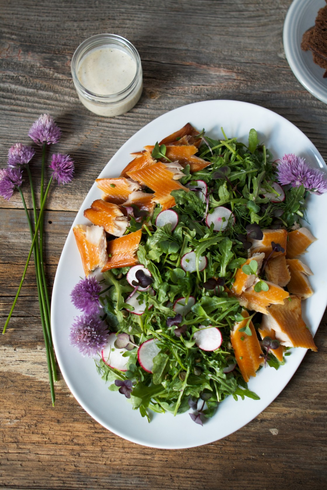 Overhead photo of a white plate with greens, smoked trout, and chive blossoms. Set on a wood table