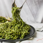 Pesto covered noodles being pulled up from a black plate on marble