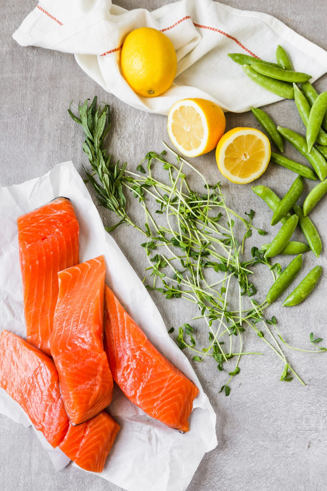 raw salmon fillets, snap peas, lemons, pea shoots, and tarragon arranged on a gray backgound