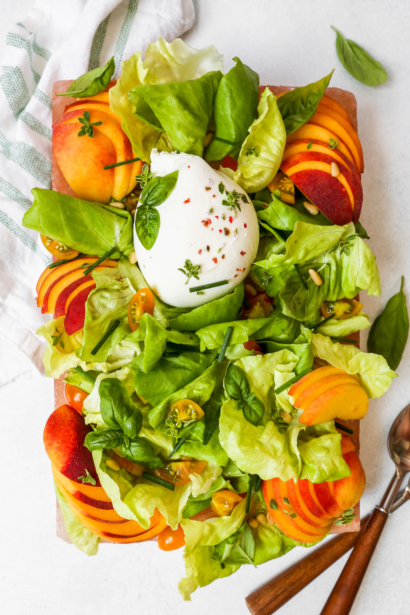 Simple summer salad with peaches, herbs, and burrata arranged on a pink platter, or salt block, set on a white surface.