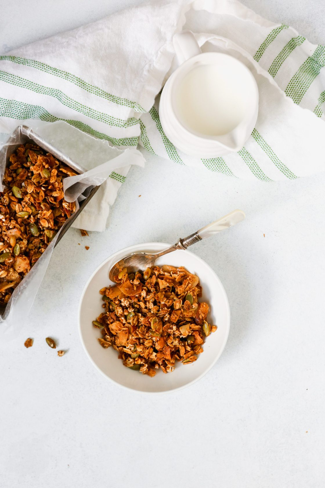Homemade healthy granola recipe in a white bowl and in a metal tin