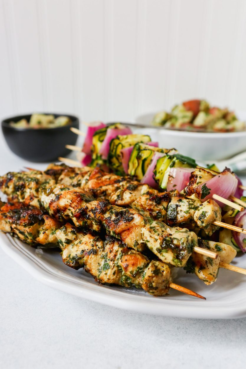 Chicken and vegetable skewers piled on a white platter with a green and white napkin.