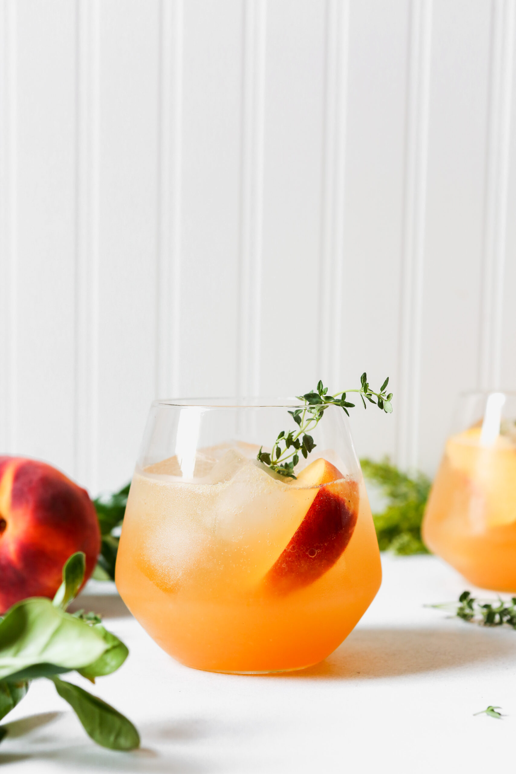 Peach and thyme cocktails set on a marble surface
