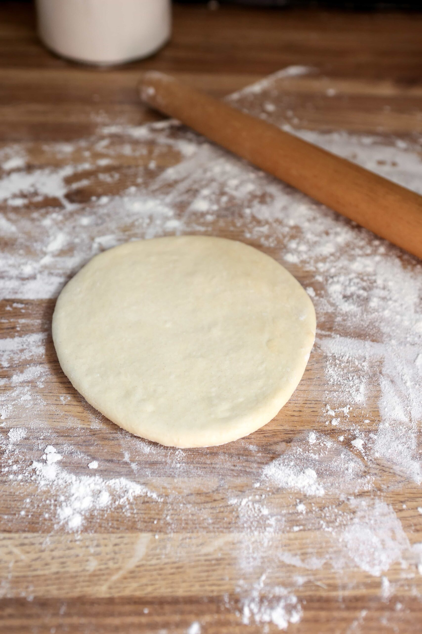 naan dough partially rolled out on floured surface