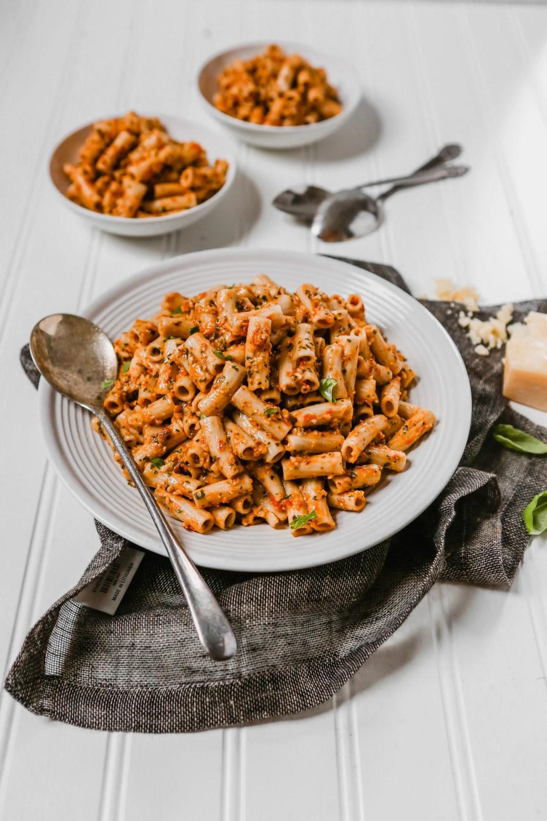 Photography of Trapanese pesto pasta piled into a white bowl with a dark napkin around it