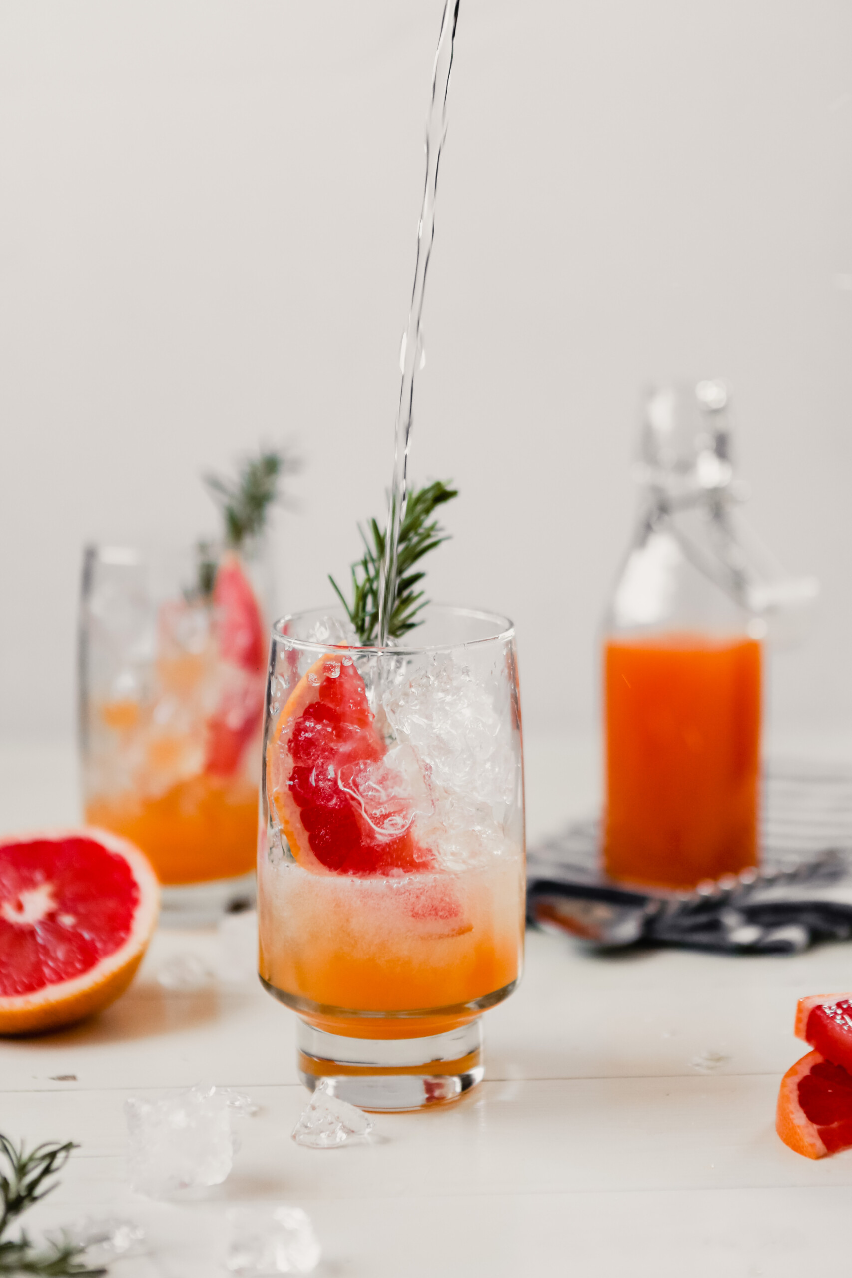 Photograph of club soda being pouring into .a glass with a grapefruit slice and sprig of rosemary to make a grapefruit soda.