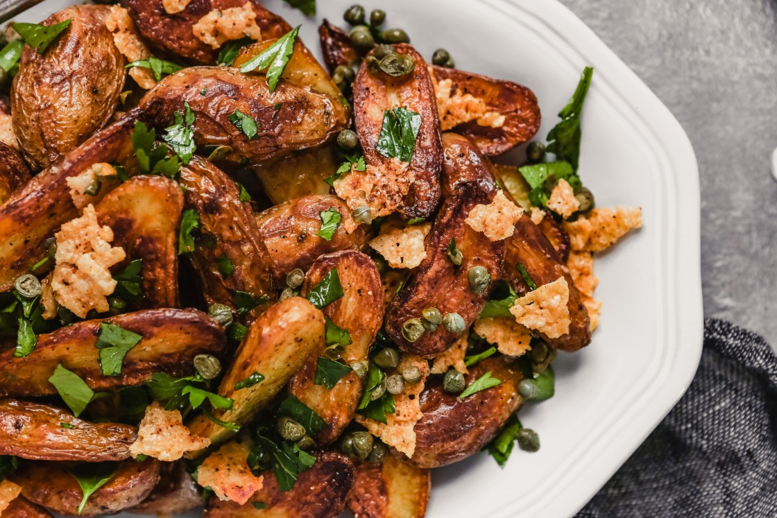 Photograph of crispy fingerling potatoes on a white oval plate set on a gray table.