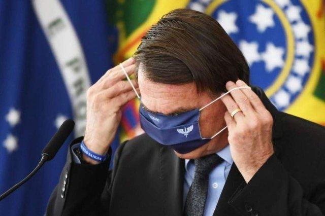 Bolsonaro tentando colocar a máscara