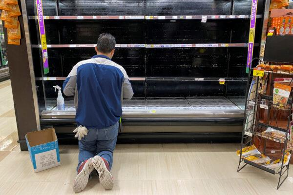 Worker cleans an empty display for eggs inside a Ralphs supermarket in Los Angeles, Calif., on March 15, 2020