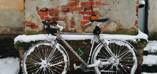 велосипед у стены зимой в снегу и сугробе
