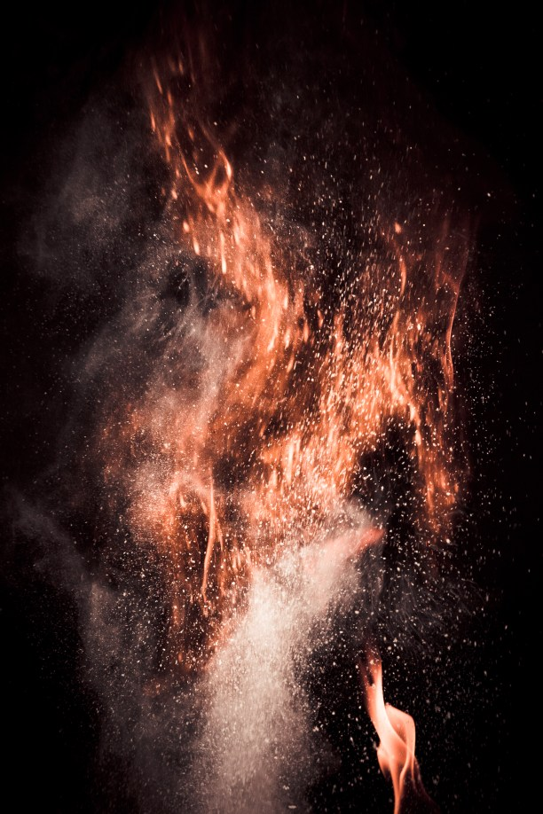 Ignited corn flour against a black backdrop.