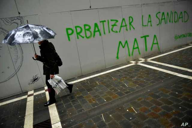 A woman shelters from the rain under an umbrella while passing graffiti reading,''Privatizing Health Service kills…