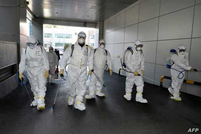 This handout picture taken Feb. 19, 2020, by Daegu Metropolitan City Namgu shows workers in protective suits spraying disinfectant in front of the Daegu branch of the Shincheonji Church of Jesus in the southeastern city of Daegu, South Korea.