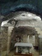 """Wnętrze groty z ołtarzem zawierającym napis: """"Hic Verbum caro factum est"""" czyli """"Tu Słowo stało się ciałem""""."""