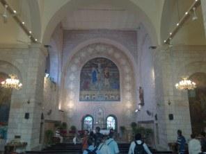 Wnętrze kościoła z mozaiką w ołtarzu głównym, przedstawiającą scenę Maryi i umiłowanego ucznia Jezusa stojących pod krzyżem.