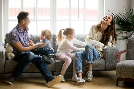 DIR Floortime Model - Happy parents and kids having fun tickling sitting together on sofa, cheerful couple laughing playing game with little active children son and daughter in living room at home, family funny activity