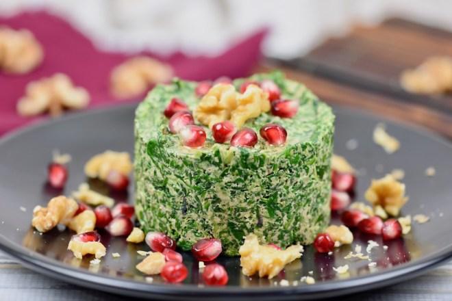 Titelbild von Zimt & Chili: Pkhali mit Spinat auf schwarzem Teller mit Walnüssen und Granatapfelkernen garniert.