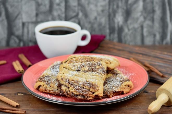 Glutenfreie Franzbrötchen auf rotem Teller. Im Hintergrund sieht man Zimtstangen, eine weiße Tasse gefüllt mit Kaffee und ein Stück von einem Nudelholz. Der Hintergrund ist dunkel.