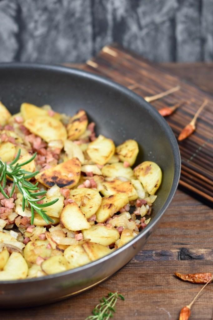 Knusprige Bratkartoffeln mit Speck und Zwiebeln in einer Pfanne, garniert mit Rosmarin - die Pfanne ist nur halb zu sehen