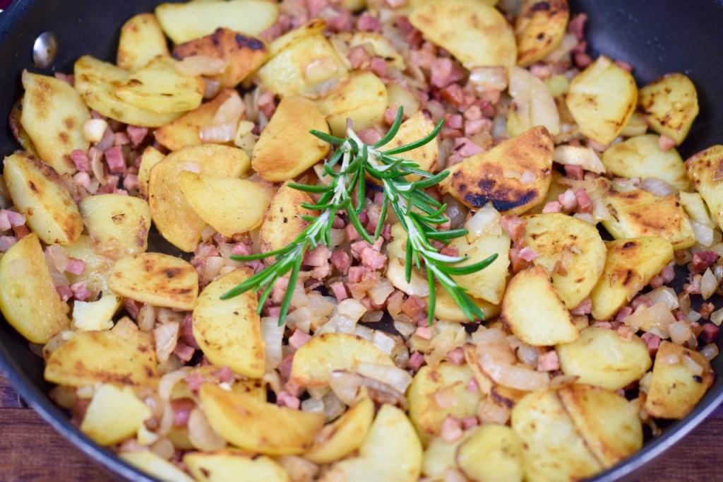 Knusprige Bratkartoffeln mit Speck und Zwiebeln in einer Pfanne, garniert mit Rosmarin - Nahaufnahme